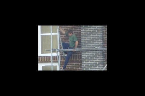 Man balancing on scaffold pole